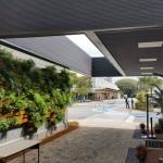 A grande cobertura em balanço abriga o acesso ao ambulatório e traz luz para a parede verde.