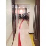 Área de passagem marcada com projeto de piso que direciona o olhar por todo o escritório